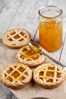 Frische gebackene törtchen mit marmeladenfüllung und aprikosenmarmelade im glasgefäß auf schneidebrett auf rustikalem holztisch.