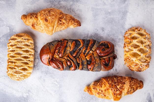 Frische gebäckoberfläche. croissants und korbbrötchen mohn. ansicht von oben