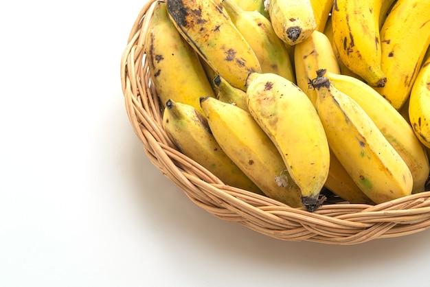 Frische gelbe bananen im korb isoliert auf weißem hintergrund