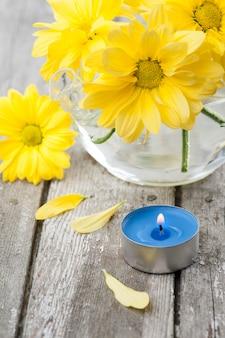 Frische gelbe gänseblümchenblumen und blau beleuchtete kerze