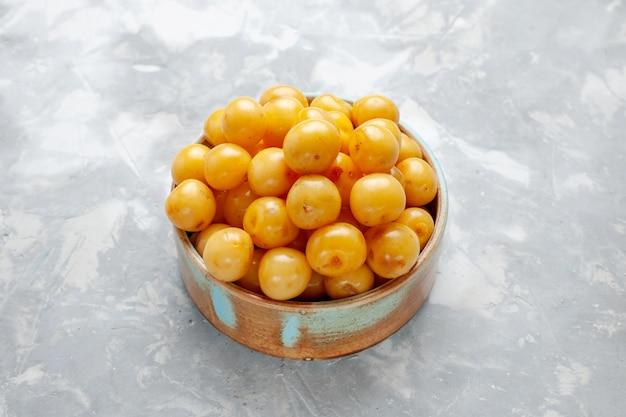 Frische gelbe kirschen in brauner schüssel auf grau-hellem schreibtisch, fruchtfrischer sommer reif