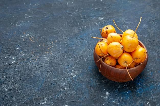 Frische gelbe kirschen reife und süße früchte auf dunklen, fruchtfrischen milden süßkirschen
