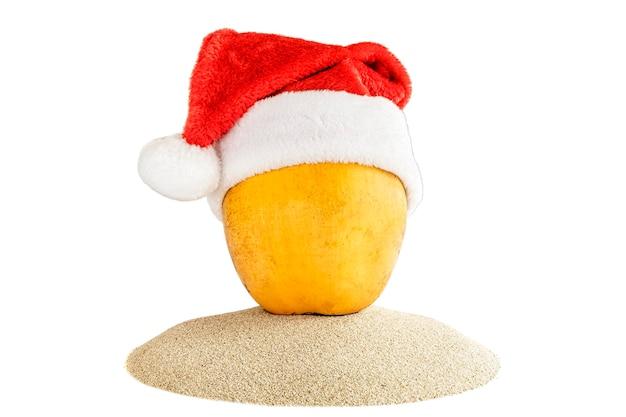 Frische gelbe kokosnuss in einer roten weihnachtsmannmütze auf sand. tropisches sommerkonzept des feiertags.