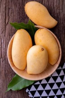 Frische gelbe mangos auf küchentisch.