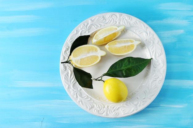 Frische gelbe zitronen mit blättern auf einer platte auf blauem hölzernem hintergrund