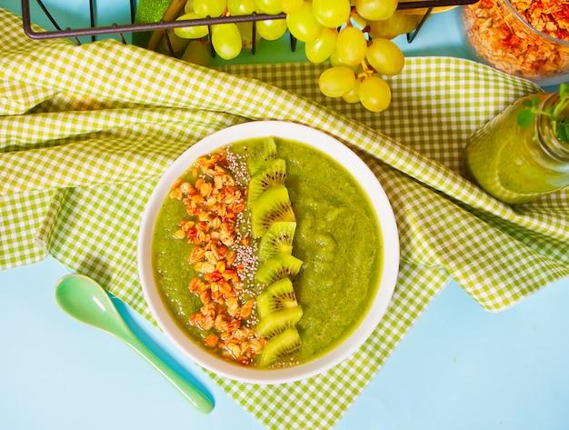 Frische gemischte grüne smoothie-schüssel mit müsli und chiasamen. gesundheits- und entgiftungskonzept. draufsicht.