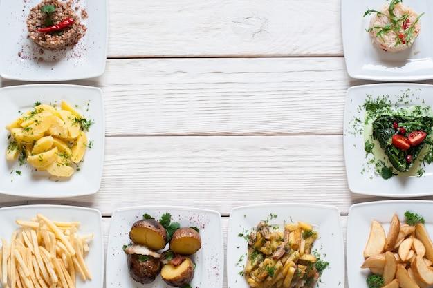 Frische gemüsesnacks auf freiem platz des weißen tisches. rahmen von tellern mit vegetarischem essen. gesund