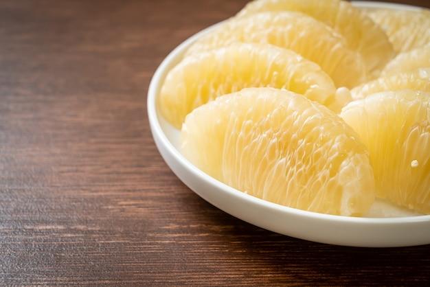 Frische geschälte pomelo, grapefruit oder shaddock auf weißem teller