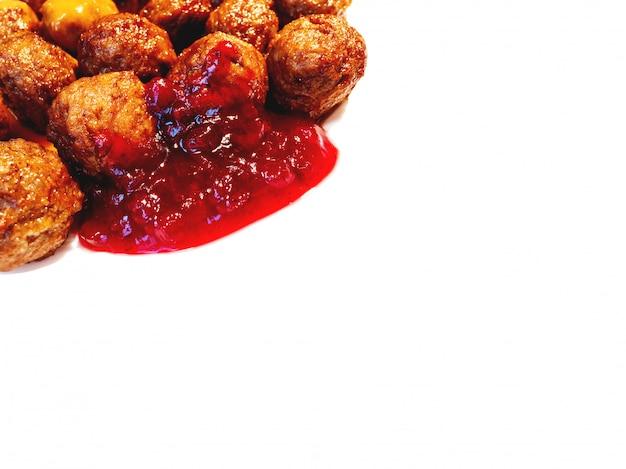Frische geschmackvolle fleischklöschen mit preiselbeersoße auf weißem hintergrund. platz für text.