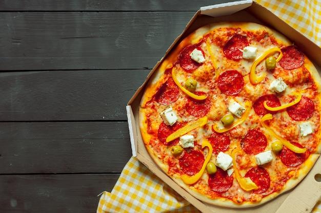 Frische geschmackvolle pizza auf hölzernem