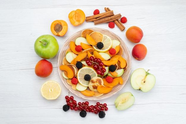 Frische geschnittene früchte der draufsicht bunt und reif mit ganzen früchten auf dem hölzernen schreibtisch und dem weißen hintergrundfruchtfarbfutterfoto