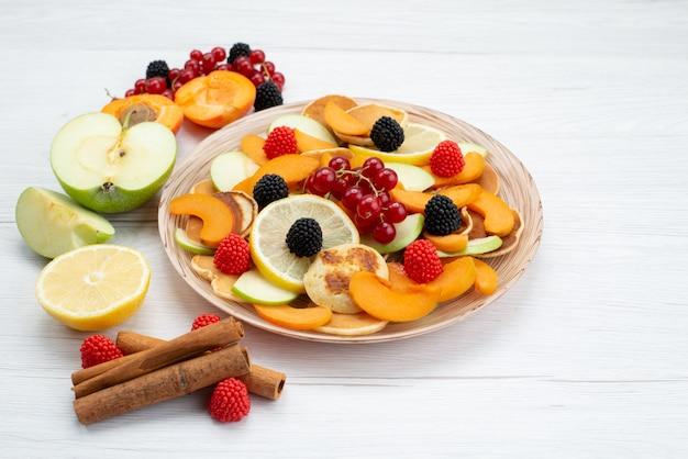 Frische geschnittene früchte der vorderansicht bunt und reif auf dem hölzernen schreibtisch und dem weißen hintergrundfruchtfarbfutterfoto