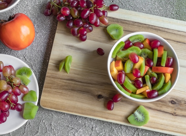 Frische geschnittene früchte im salat auf dem hölzernen hintergrund. trauben, persimone und kiwi