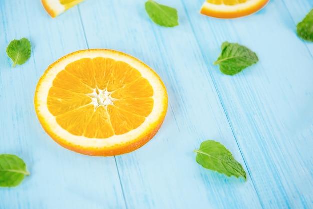 Frische geschnittene orangen mit pfeffer verlässt auf hellblauem hölzernem hintergrund