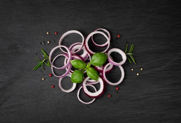 Frische geschnittene rote zwiebel auf schwarzem hintergrund draufsicht