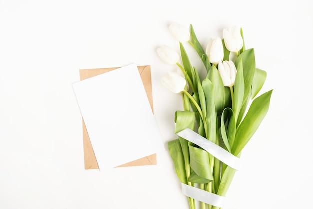 Frische geschnittene weiße tulpenblumen und leere karte mit umschlag draufsicht auf weißem hintergrund