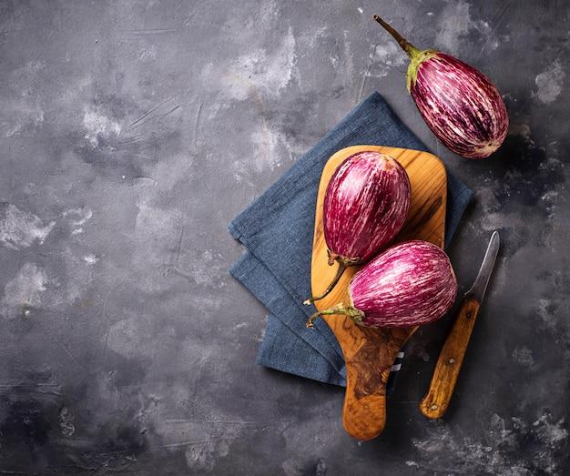 Frische gestreifte purpurrote auberginen auf grauem hintergrund