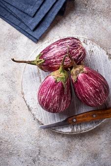 Frische gestreifte purpurrote auberginen auf hellem hintergrund