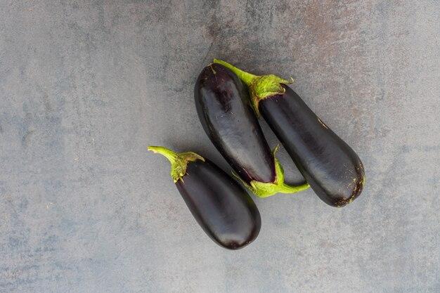 Frische gesunde auberginen auf dunklem holzhintergrund.
