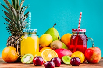 Frische gesunde Früchte und Saftmaurergläser auf Tabelle gegen blauen Hintergrund