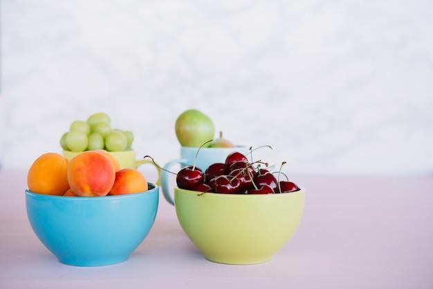 Frische gesunde früchte in der schüssel auf weißer oberfläche
