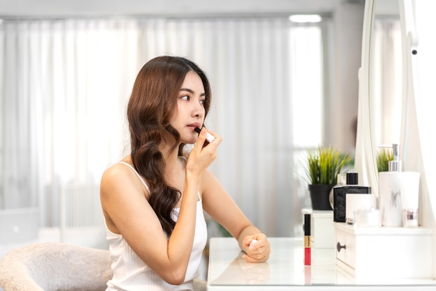 Frische gesunde haut der lächelnden schönen asiatischen frau, die auf spiegel schaut und genießt, lippen mit rotem lippenstift zu hause aufzutragen. gesichtsschönheit