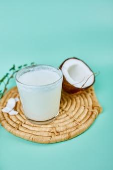 Frische gesunde kokosmilch in einem glas auf blauer oberfläche, alternative art von veganer milch, bio-gesundes-getränkekonzept.