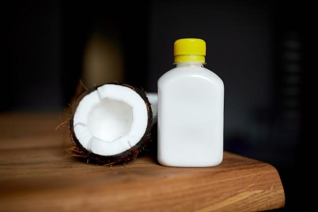 Frische gesunde kokosmilch in einem glas auf holztisch, alternative art von veganer milch, bio-gesundes getränkekonzept