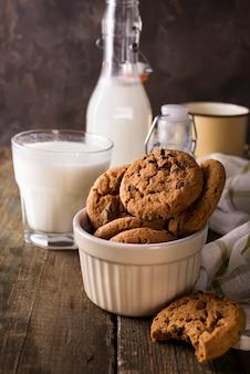 Frische gesunde milch und kekse auf einem rustikalen hölzernen hintergrund