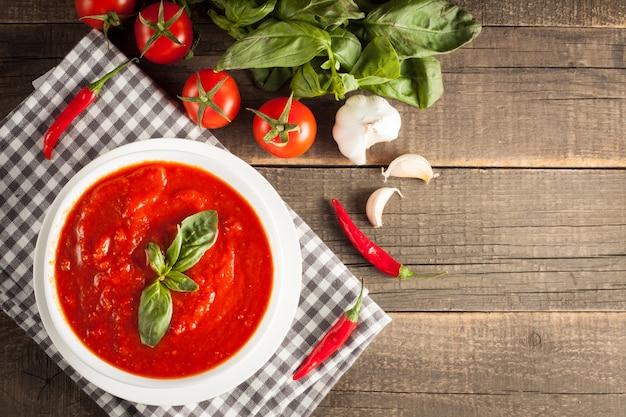 Frische, gesunde tomatensuppe mit basilikum, tomaten auf hölzernem hintergrund. spanische gazpacho-suppe.