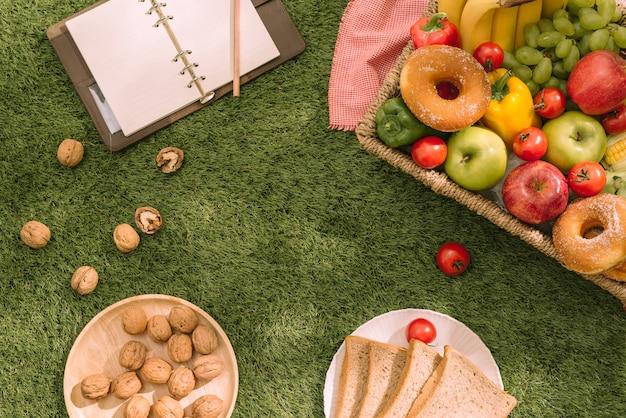 Frische gesunde tropische früchte auf einer picknickdecke auf dem gras mit trauben, apfel, grapefruit, orange und banane