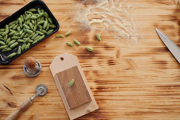 Frische gnocchi-nudeln mit teigwerkzeugen. frische hausgemachte pasta auf dem tisch zubereiten