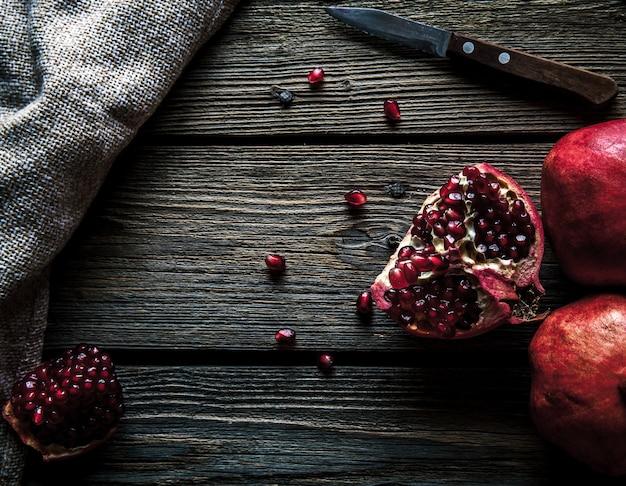 Frische granatäpfel auf einem holztisch. bio, obst, essen