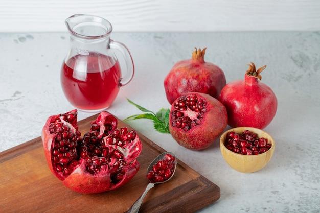 Frische granatäpfel. ganze oder geschnittene granatäpfel auf holzbrett über grauer wand.