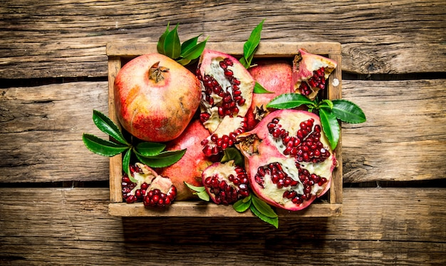 Frische granatäpfel in einer alten schachtel mit blättern. auf hölzernem hintergrund. draufsicht