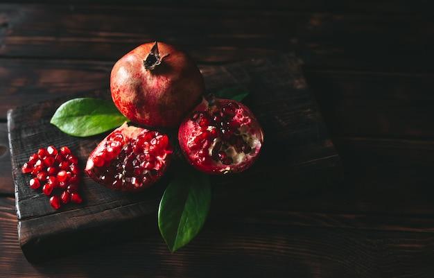 Frische granatapfelfrüchte als ganzes und auf einem rustikalen holztisch geschnitten