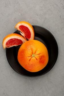 Frische grapefruit in scheiben geschnitten und ganz frisch in schwarzer platte auf grauem boden