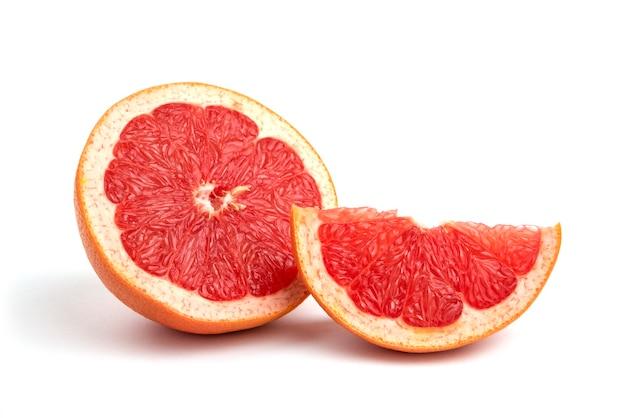 Frische grapefruit isoliert auf weißer oberfläche ganz oder in scheiben geschnitten.