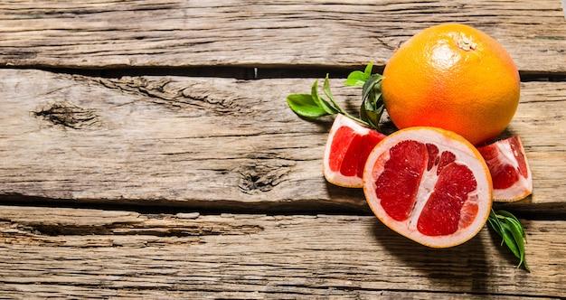 Frische grapefruit mit blättern. auf einem holztisch. freier platz für text. draufsicht