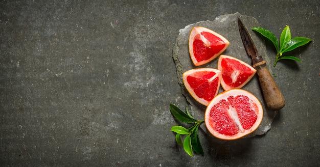 Frische grapefruit mit blättern und messer auf einem steinständer. auf dem steintisch. freier platz für text. draufsicht