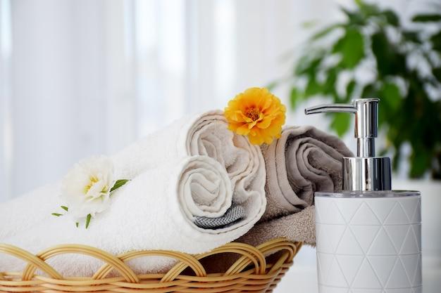 Frische graue und weiße handtücher in korbgeflecht, verziert mit blumen und flüssigkeitsbehälter.