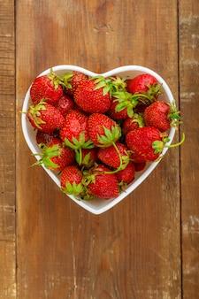 Frische große erdbeeren in einem herzförmigen teller. vertikales foto