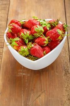 Frische große erdbeeren in einem herzförmigen teller.