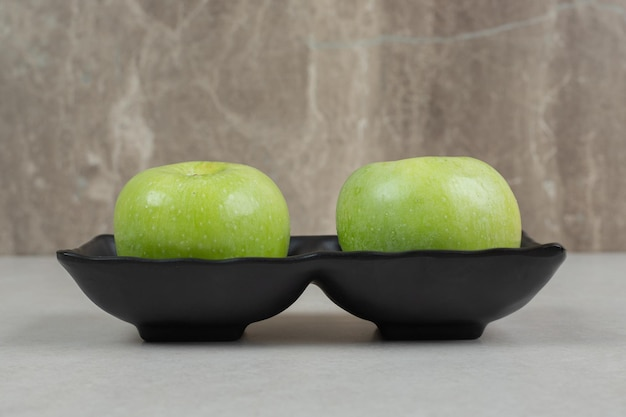 Frische grüne äpfel auf schwarzem teller.
