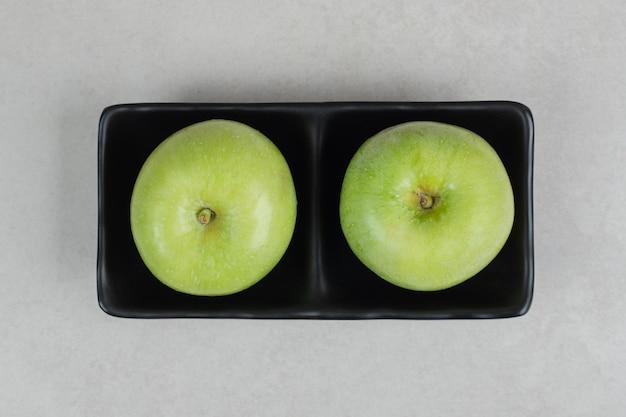 Frische grüne äpfel auf schwarzem teller