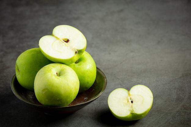 Frische grüne äpfel halbiert in schwarze schüssel auf dunklem hintergrund
