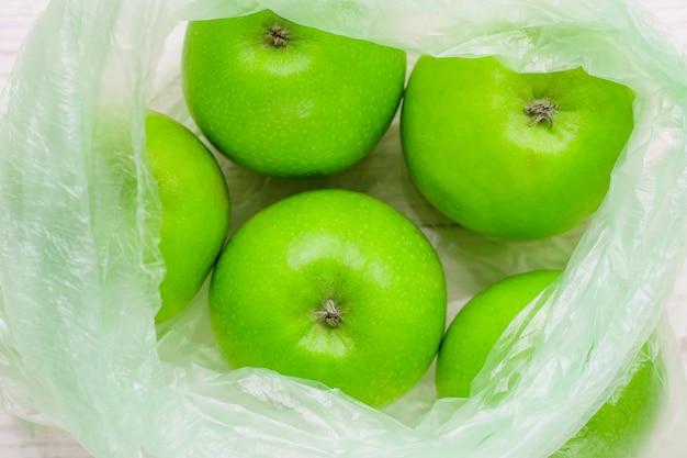 Frische grüne äpfel in der plastiktasche auf holztisch. umweltkonzept der nicht-ökologischen verwendung von kunststoff