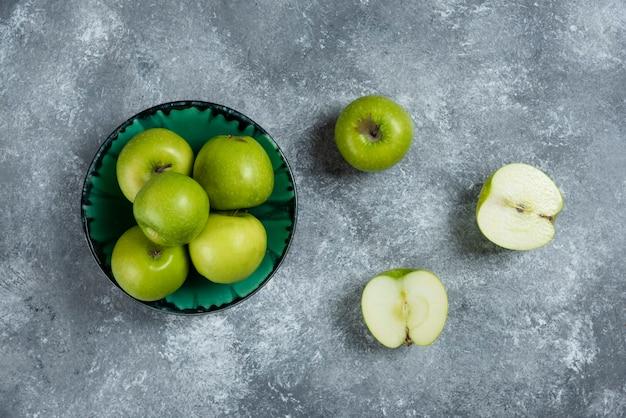 Frische grüne äpfel in grüner schüssel.