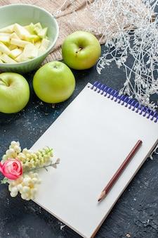 Frische grüne äpfel weich und saftig mit geschnittenem apfel in teller auf dunkelblauem schreibtisch, obst frische lebensmittel gesundheit vitamin