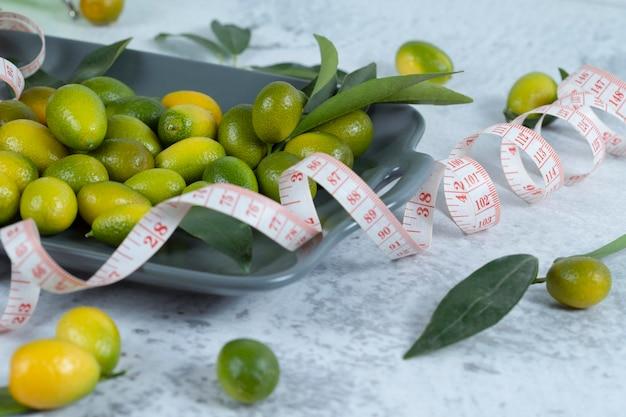 Frische grüne cumquats mit maßband und blättern auf marmorhintergrund gelegt. hochwertiges foto
